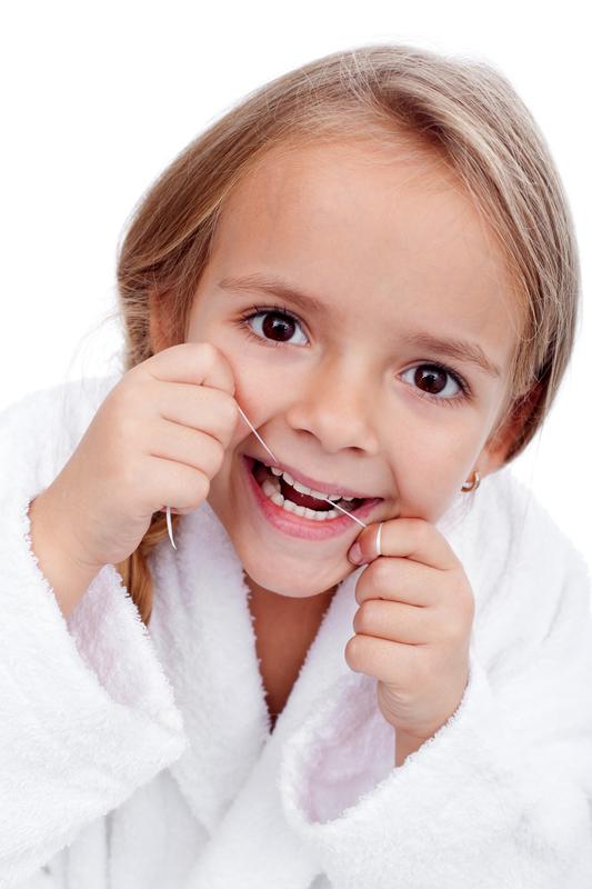 devojčica koristi zubni konac
