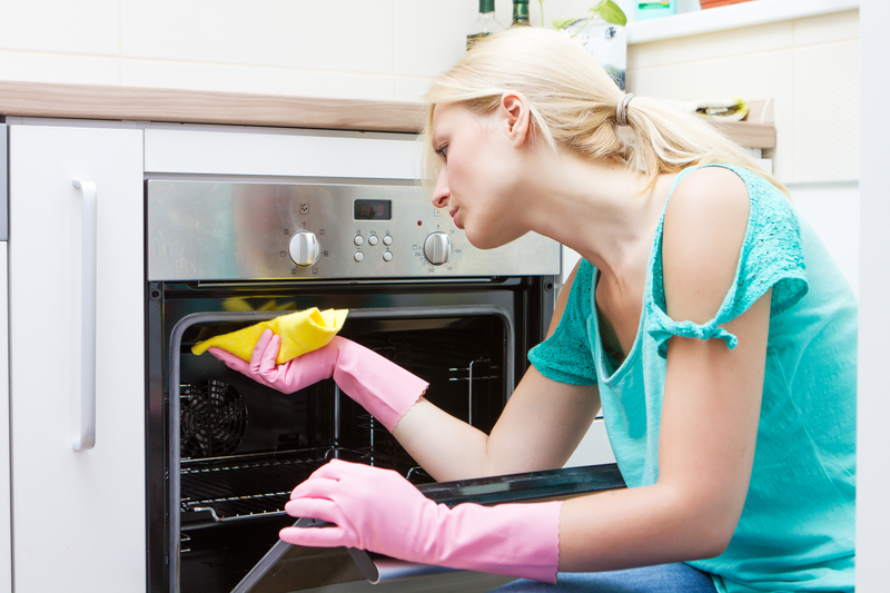 http://www.dreamstime.com/stock-photography-young-woman-cleaning-oven-kitchen-image31851852