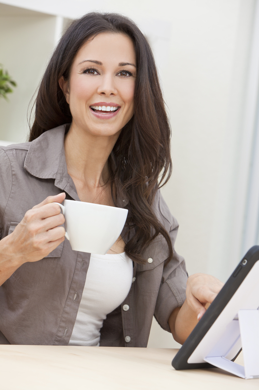http://www.dreamstime.com/stock-images-woman-using-tablet-computer-drinking-tea-coffee-image22314484