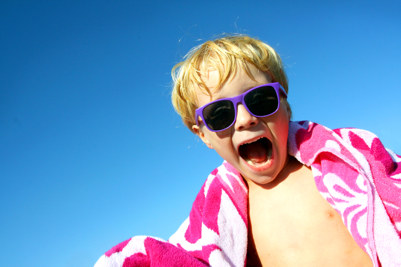 http://www.dreamstime.com/royalty-free-stock-photo-hip-excited-child-beach-towel-sunglasses-young-boy-has-big-smile-his-face-as-stands-outside-wrapped-bright-pink-image33921755