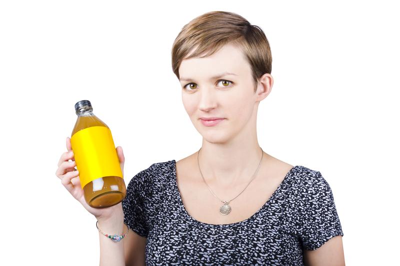 Woman holding glass bottle of apple cider vinegar