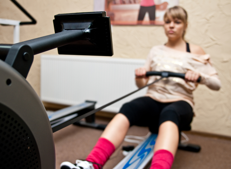 http://www.dreamstime.com/stock-photo-woman-using-rowing-machine-young-gym-image36018960